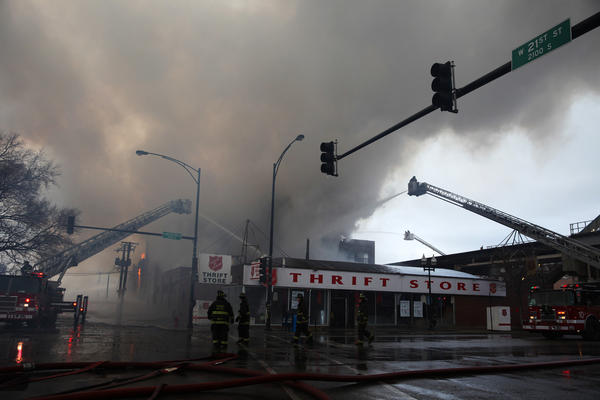 A huge plume of smoke rises over a Salvation Army thrift store on 21st Street next to a warehouse that caught fire.