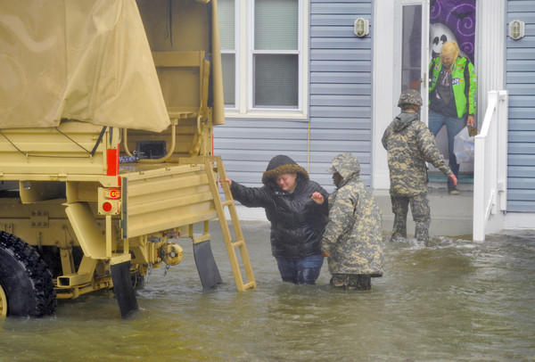 A military truck sits in the water on St. Louis Avenue between 8th and 9th Streets as personnel help residents (two women, one man and family pet) evacuate amid Hurricane Sandy's flooding.