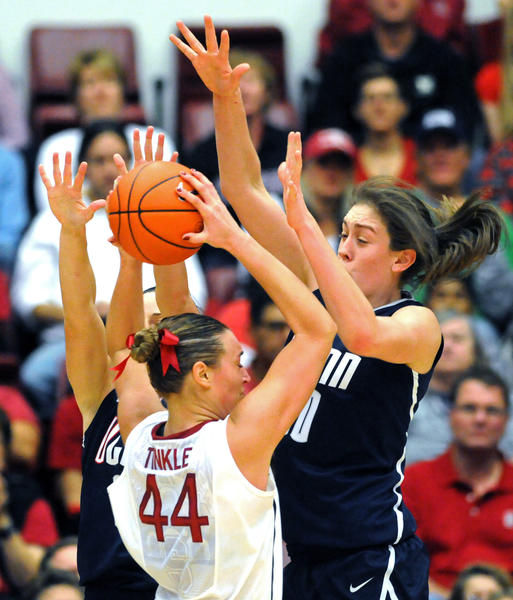 UConn's Kelly Faris, back left, and Breanna Stewart defend Stanford's Joslyn Tinkle at Roscoe Maples Pavilion Saturday afternoon. The Huskies held the Cardinal to 19 percent from the field.