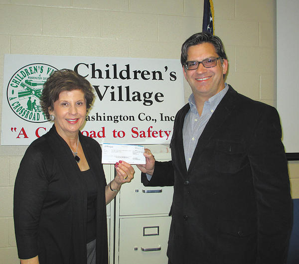 From left, Rochelle Morrell, executive director of Children's Village, accepts a $3,000 check from Timothy Curtis, field engineering group manager for FM Global.