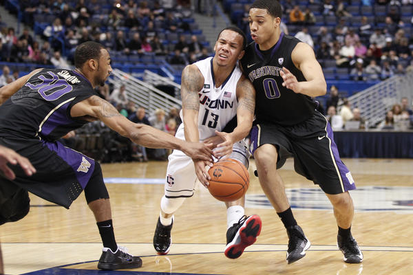 UConn guard Shabazz Napier drives between Washington's Desmond Simmons (30) and Abdul Gaddy during the first half at the XL Center.