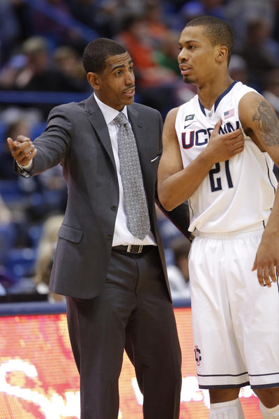 UConn coach Kevin Ollie talks with guard Omar Calhoun as they take on the Washington Huskies during the second half at the XL Center.