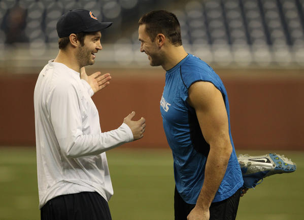 Jay Cutler laughs with Lions tight end Tony Scheffler before the start of their game.