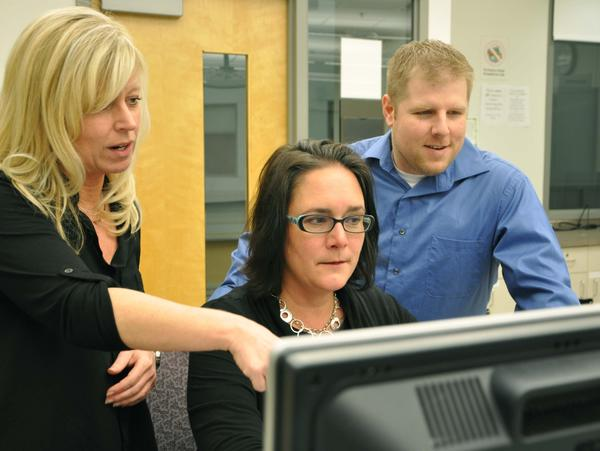 Anne Arundel Community College instructional specialist Dawn Blanche, left, works with students Marcelle Lee and Dustin Shirley, who recently recently won the community college division of a U.S. Department of Defense cyber crime competition. The contest challenges students to analyze digital clues related to cyber security and terrorism issues.