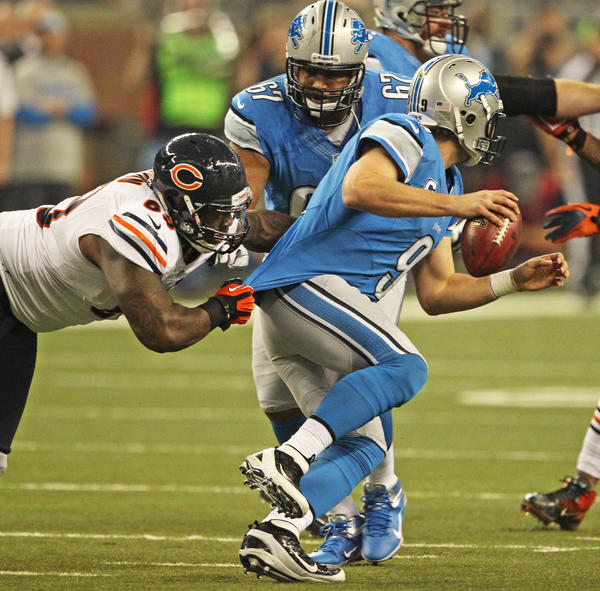 Defensive tackle Henry Melton gets his hands on Lions quarterback Matthew Stafford's jersey but he is unable to sack him during the first quarter.