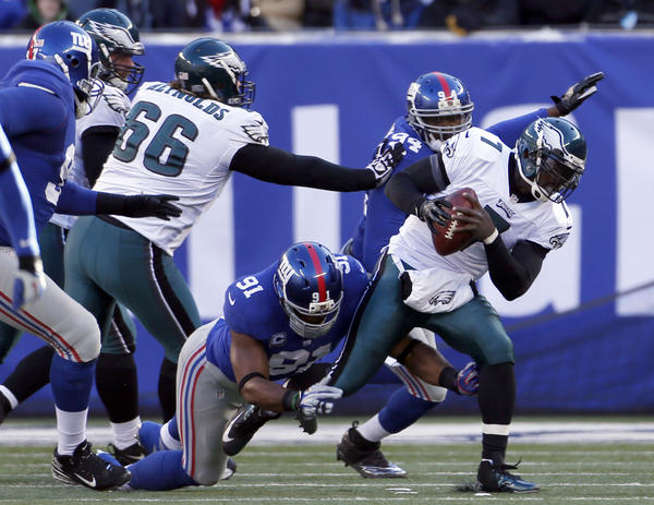Philadelphia Eagles quarterback Michael Vick (7) is sacked by New York Giants defensive end Justin Tuck (91) in the first half during the game at Metlife Stadium.