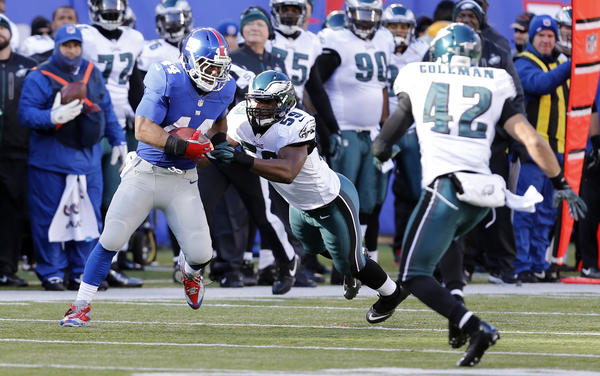 New York Giants running back Ahmad Bradshaw (44) runs past Philadelphia Eagles middle linebacker DeMeco Ryans (59) during the game at Metlife Stadium.