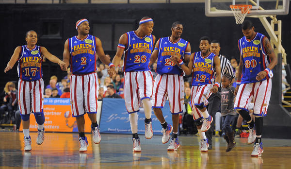 The Harlem Globetrotters squad hold hands with Chelsea Williams, 5, of Randallstown during their performance.