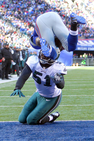 New York Giants running back David Wilson (22) scores a touchdown over Philadelphia Eagles linebacker Jamar Chaney (51) during the first quarter of an NFL game at MetLife Stadium.