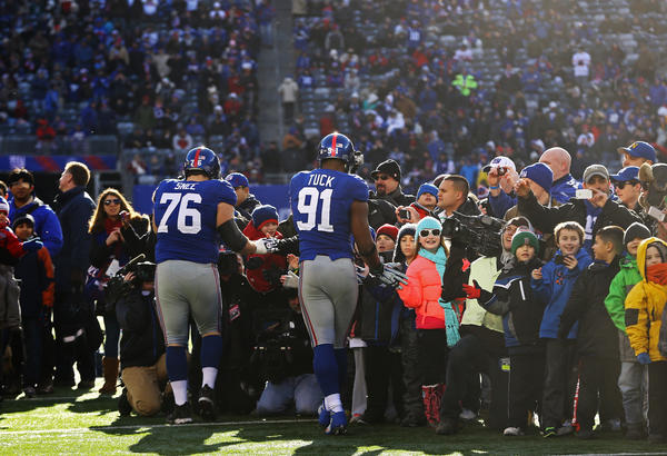 Giants players Chris Snee (76) and Justin Tuck greet members of the Sandy Hook Elementary School community ring the field prior to the start of Sunday's Giants-Eagles game.