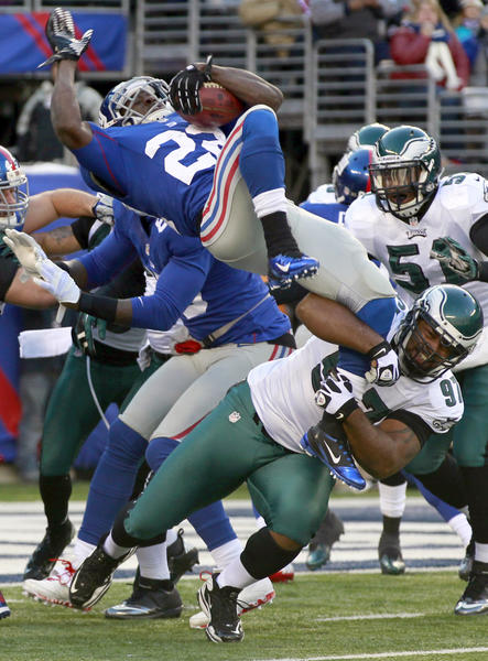 Philadelphia Eagles defensive tackle Cullen Jenkins (97) tackles New York Giants running back David Wilson (22) behind the line of scrimmage in the first half during the game at Metlife Stadium.