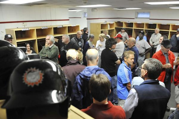 People look over the visitors locker room at Municipal Stadium during a tour of the ballpark Wednesday evening.