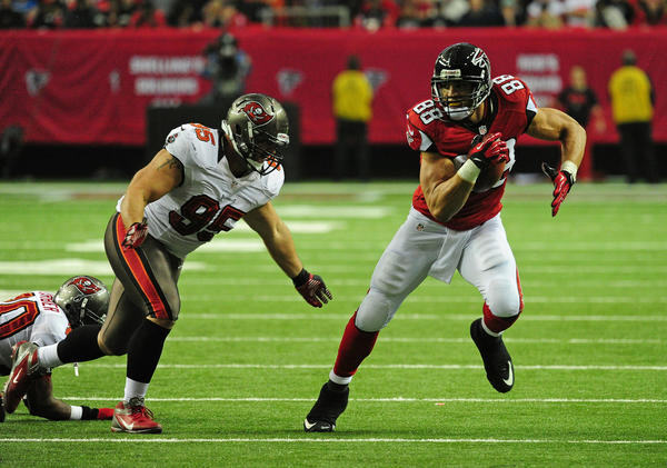 Tony Gonzalez #88 of the Atlanta Falcons runs with a catch against Gary Gibson #95 of the Tampa Bay Buccaneers at the Georgia Dome on December 30, 2012 in Atlanta, Georgia. Tampa Bay won 22–17.