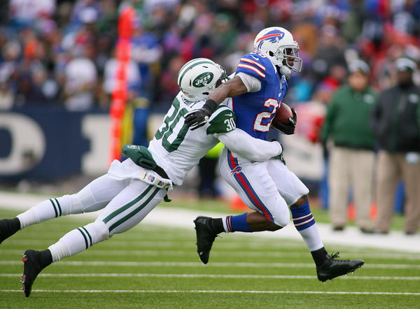 C.J. Spiller #28 of the Buffalo Bills runs with LaRon Landry #30 of the New York Jets hanging on at Ralph Wilson Stadium on December 30, 2012 in Orchard Park, New York. Buffalo won 28–9.