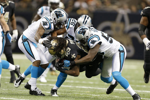 Chris Ivory #29 of the New Orleans Saints is tackled by Captain Munnerlyn #41, D.J. Campbell #26 and Thomas Davis #58 of the Carolina Panthers at Mercedes-Benz Superdome on December 30, 2012 in New Orleans, Louisiana. The Panthers defeated the Saints 44–38.
