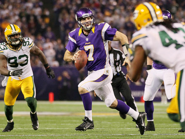 Christian Ponder #7 of the Minnesota Vikings runs from Green Bay Packers defenders during the third quarter on December 30, 2012 at Mall of America Field at the Hubert H. Humphrey Metrodome in Minneapolis, Minnesota. The Vikings defeated the Packers 37–34.