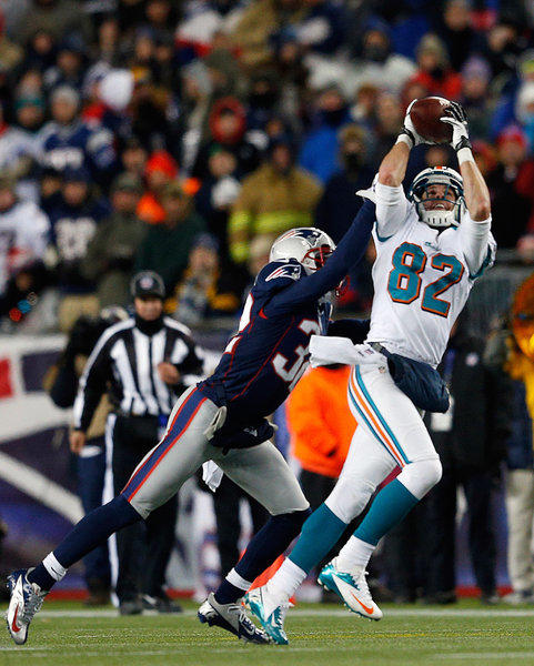 Brian Hartline #82 of the Miami Dolphins is defended Devin McCourty #32 of the New England Patriots in the second half at Gillette Stadium on December 30, 2012 in Foxboro, Massachusetts. New England won 28–0.