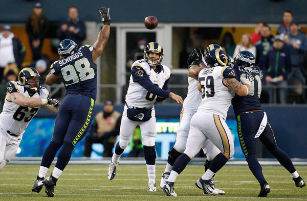 Sam Bradford #8 (M) of the St. Louis Rams throws late in the second half against the Seattle Seahawks at CenturyLink Field on December 30, 2012 in Seattle, Washington. Seattle won 20–13.