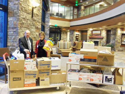 Gordon Larson, left, CEO of Sanford Aberdeen Medical Center, and Lisa Kopecky, director of nutrition and food service, are shown organizing boxes of food in the lobby of Sanford Aberdeen Medical Center during a recent food drive challenge on behalf of Safe Harbor in Aberdeen.