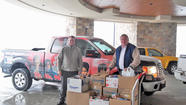 Radio station personnel deliver food donations