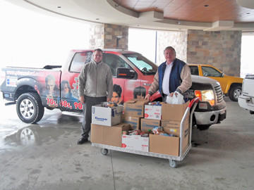 Dakota Broadcasting general manager Joel Swanson, left, and sales manager Devin Reints delivered boxes of nonperishable food donations during a recent food drive challenge on behalf of Safe Harbor in Aberdeen.