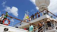 Passengers stand at the rails as the Carnival Valor sails into Aruba.
