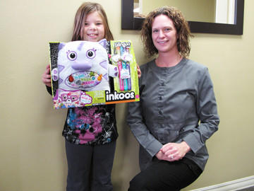 Madison Miller, left, seen with Dr. Amy Scepaniak, won an Inkoos on Nov. 1 for donating her Halloween candy at Smile Solutions' annual Halloween candy buy-back event. The candy was sent to troops serving overseas via Operation Gratitude.