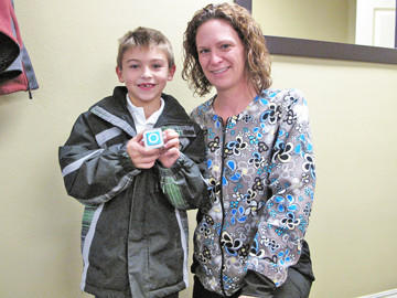 Jake Kraft, left, is seen with Dr. Amy Scepaniak after winning an iPod on Nov. 1 for donating his Halloween candy at Smile Solutions' annual Halloween Candy buy-back. The candy is sent to troops serving overseas via Operation Gratitude.