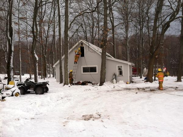 Firefighters on scene of a house fire in McKinley Township today, Monday.