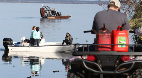 Family and friends of the the two missing boaters conduct their own search Monday,left,on Lake Jessup and on land by ATV's.
