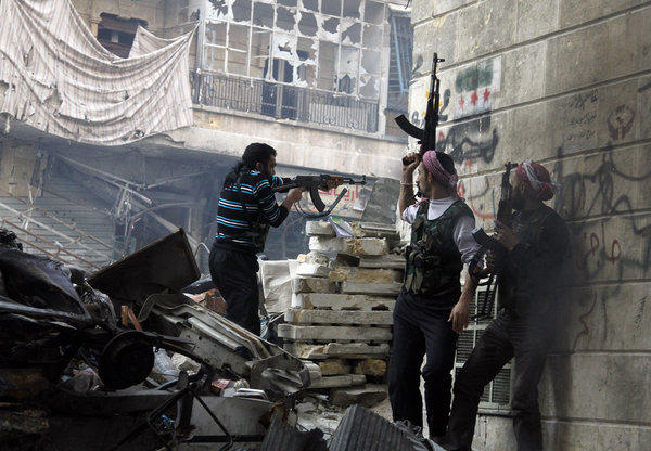 Rebel fighters from the Free Syrian Army fire at enemy positions during heavy clashes with government forces in the Salaheddine district of Aleppo on Saturday.