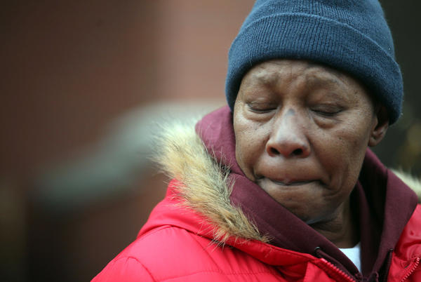 Willie Beler, mother of Nathaniel Beler, closes her eyes while speaking outside the fire scene.