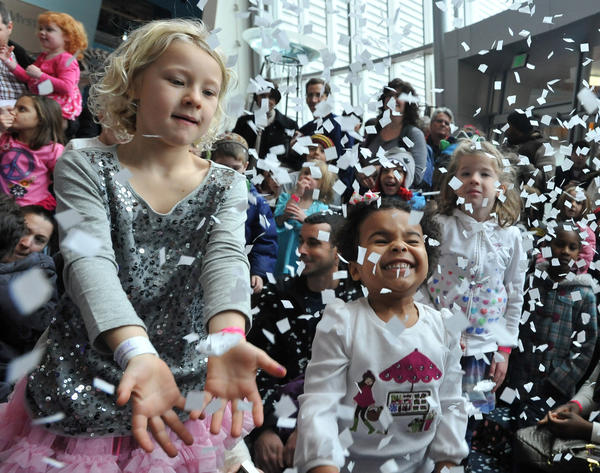 Charlotte Marshall, left, and Stella Rose Dorazio, right, celebrate New Year's Eve early with the band Milkshake and a ball drop with confetti on Dec. 31 at the Maryland Science Center,