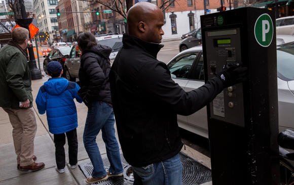 Ron Dubois of Chicago pays for parking Friday. Tribune photo