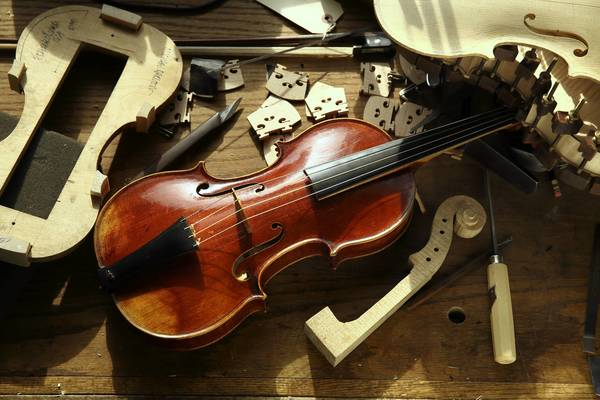 "A violin hand-made by Michael Darnton in Darnton's Loop studio surrounded by pieces of an unfinished violin. The finished violin, made in 2008, is a ""long Strad,"" crafted in 2008 by Darnton and modeled on one of Stradivarius's slightly longer violins of the year 1695."