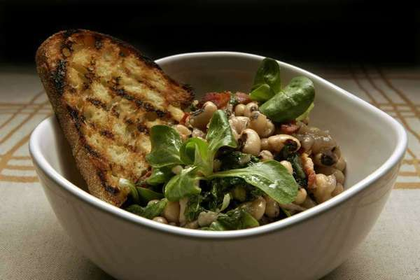 A warm salad of black-eyed peas with wilted greens and bacon.