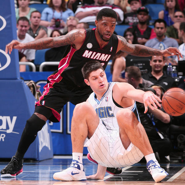Orlando center Nikola Vucevic (9) battles for a loose ball with Miami forward Udonis Haslem (40) during the second half of the Magic's 112-110 overtime loss the Heat in Orlando, Fla.