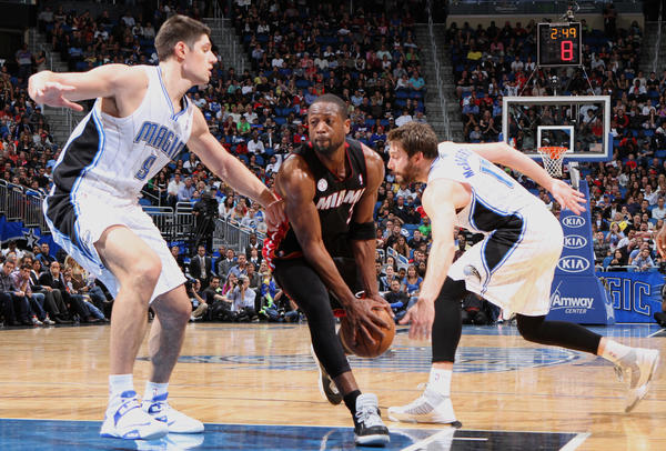 Miami guard Dwyane Wade (3) drives between Orlando's Nikola Vucevic (9) and Josh McRoberts (17) during the second half of the Magic's 112-110 overtime loss to the Heat in Orlando, Fla.