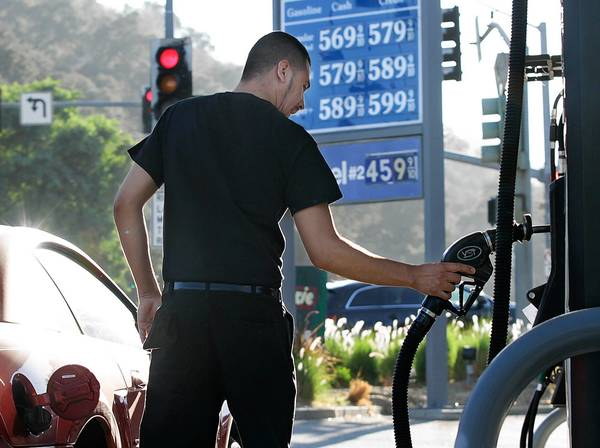 Ruben Vasquez of Pacoima finishes pumping at a station in Calabasas in October. He decided not to fill up because of the high price.