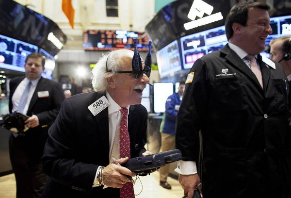 A trader at the New York Stock Exchange dons New Year's party glasses Monday.