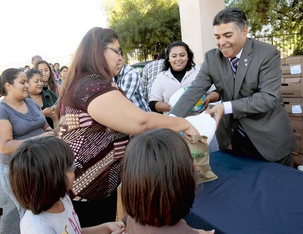 U.S. Rep.-elect Tony Cardenas hands out turkeys at the annual turkey giveaway at his council district office in Sun Valley.