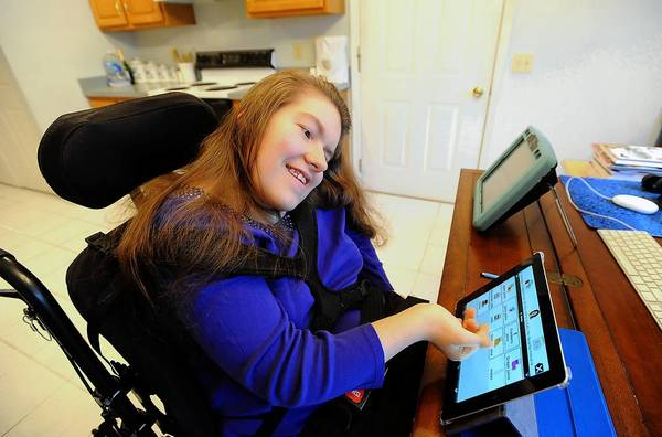 Kelly Berta, 24, of Allentown, demonstrate her Proloquo2Go app on her an Apple iPad to allow her to communicate with her family and friends.