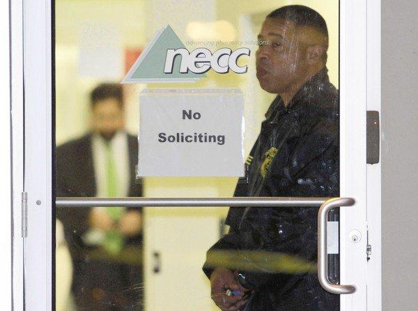An FDA agent stands at the doorway of the New England Compounding Center in Framingham, Mass., in October as investigators work inside. The company's steroid medication was linked to a deadly nationwide meningitis outbreak.
