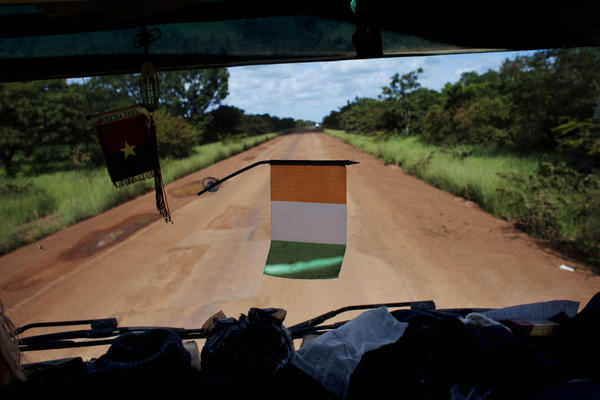 An Ivory Coast flag hangs from the dashboard of a commercial truck on the road to Ouagadougou, Burkina Faso.
