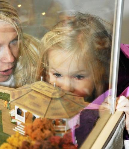 Ryleigh Zimmerman, 5, of Littlestown, studies the dancing figures at a park pavillion as her mother, Christine, explains the display in the 2012 edition of the Pleasant Valley Fire Company train garden.