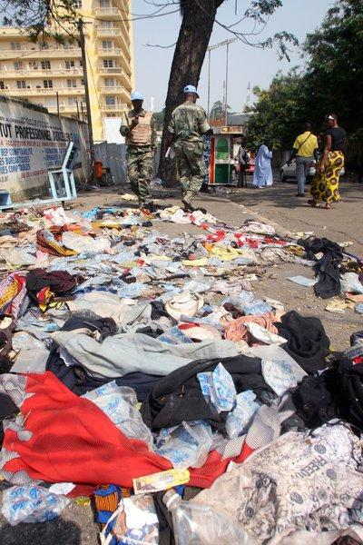 U.N. peacekeepers stand next to shoes and other items lying on the pavement at the scene of a stampede in Abidjan, Ivory Coast, on Tuesday.