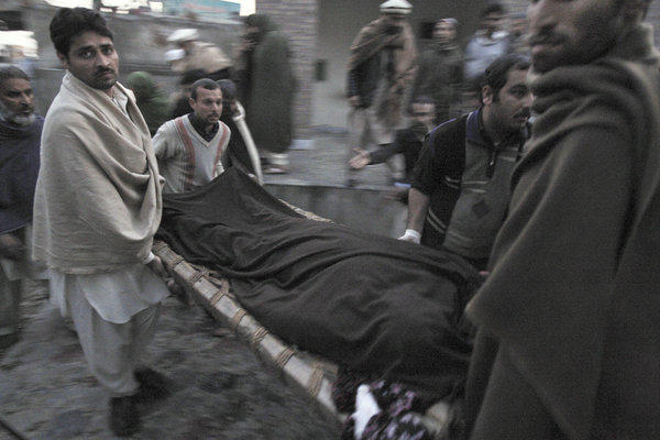 Pakistani men carry the body of a teacher who was killed Tuesday by gunmen from a hospital for burial in Swabi, Pakistan.