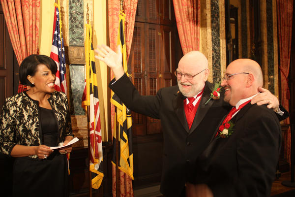 Jim Scales, a longtime manager in the Baltimore mayor's office, throws a hand in the air just after Mayor Stephanie Rawlings-Blake officiated his marriage to Bill Tasker at City Hall early New Year's Day. Their wedding was one of seven to take place at City Hall on the first day same-sex marriage was legal in the state.