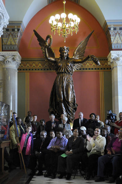 "Audience members listen to a poem being read at a celebration marking the 150th anniversary of the Emancipation Proclamation at the state Capitol Tuesday, beneath the statue ""The Genius of Connecticut"" in the North Lobby.  Lt. Gov. Nancy Wyman is standing at center and Attorney General George Jepsen is at her left."
