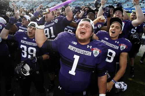 Northwestern players including defensive lineman Bo Cisek (1) celebrate with fans after their Gator Bowl win.